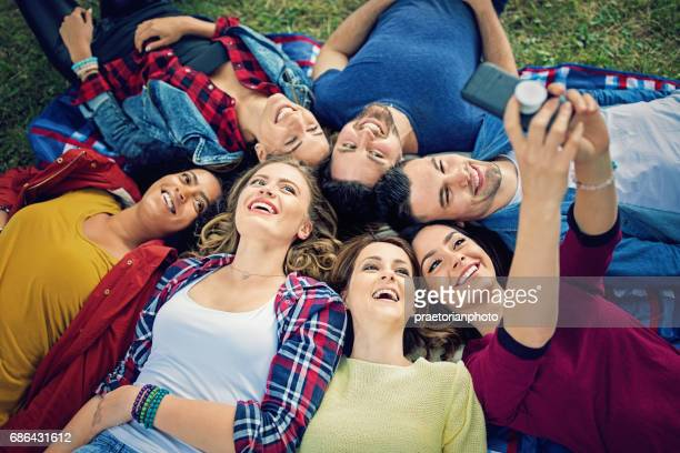 Happy friends are lying down and taking selfie in the park