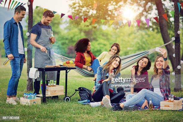 Happy friends are taking selfie at a barbecue in the park