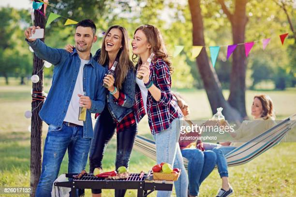 Happy friends are taking selfie/video call at a barbecue in the park