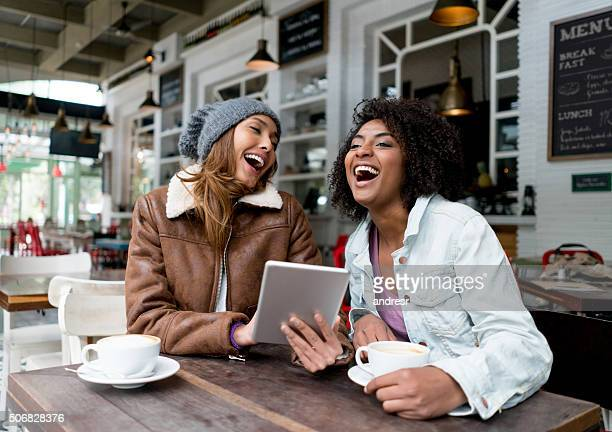 Happy friends at a cafe social networking using a tablet