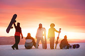 Happy friends with ski and snowboard at ski resort against sunset