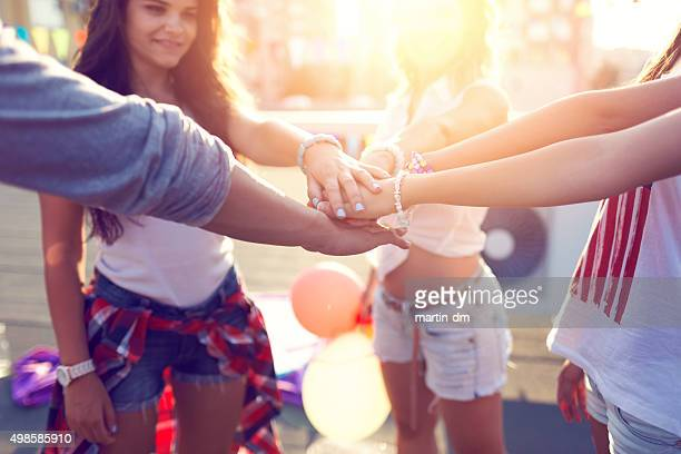 Glückliche Freunde auf der Dachterrasse putting Hände zusammen