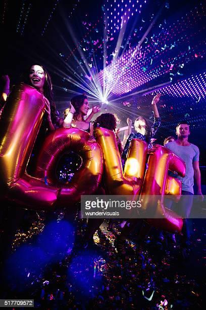 Glückliche Freunde feiern night-club Partei mit Konfetti und Ballons