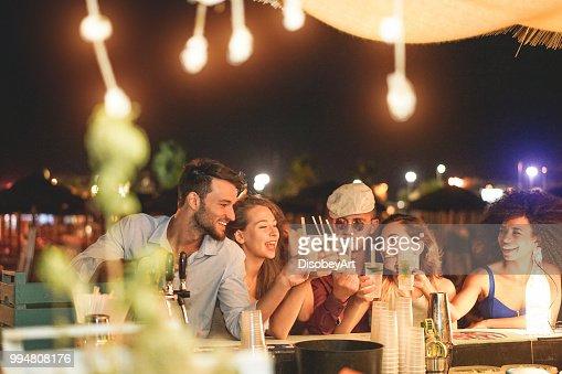 幸せな友人応援とビーチ パーティー屋外 - 週末夏夜 - 若者のライフ スタイルとナイトライフ コンセプト - メイン焦点左みんなで楽しんで若い新世紀人でカクテルを飲む : ストックフォト