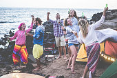 Happy friends dancing and making barbecue beach party - Adult surfer people having fun together drinking beer and camping next ocean - Focus on center man face - Fun, vacation and friendship concept