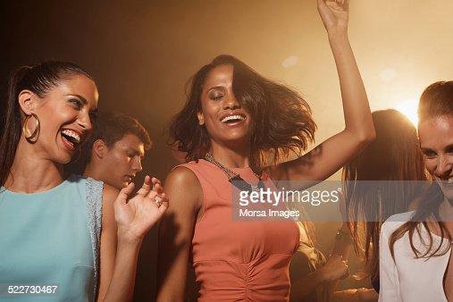 Happy friends dancing at nightclub