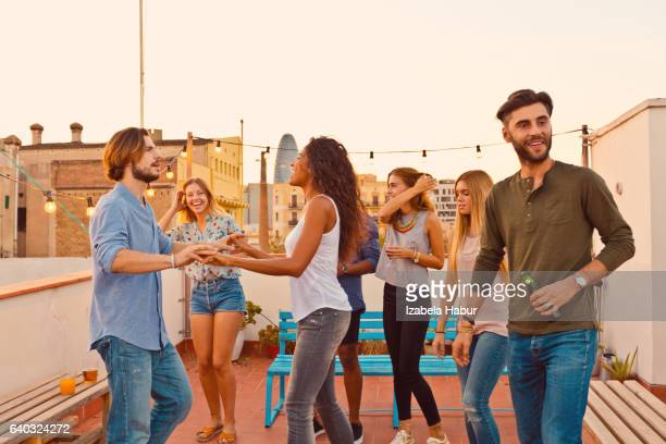 Happy friends dancing at the rooftop party