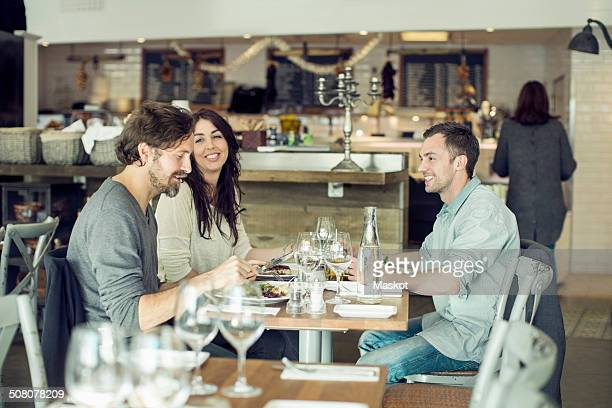 Happy friends discussing at restaurant table