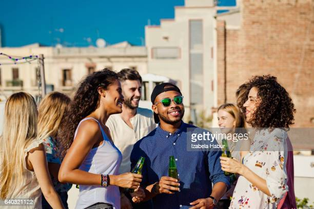 Happy friends drinking beer at rooftop party
