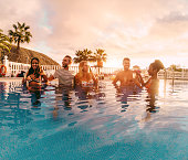 Happy friends drinking champagne in pool party at sunset - Rich people having fun in exclusive tropical vacation - Holiday, youth lifestyle and friendship concept - Main focus on left guys