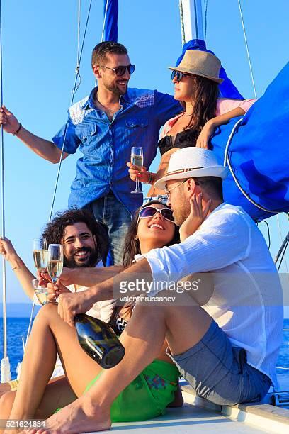 Amigos felices bebiendo champán en barco de vela
