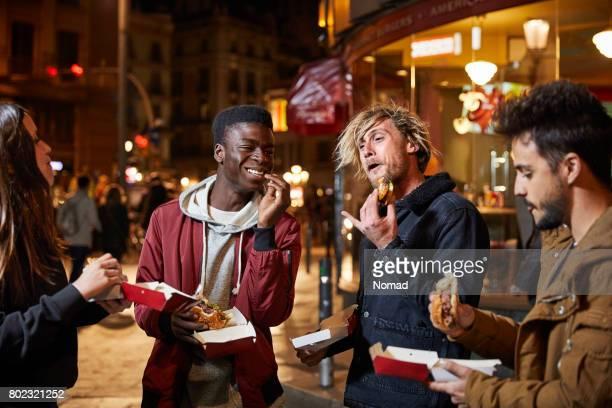 Heureux amis appréciant hamburger sur rue dans la nuit
