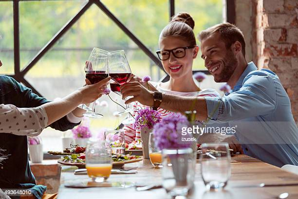 Happy friends enjoying dinner, toasting with red wine