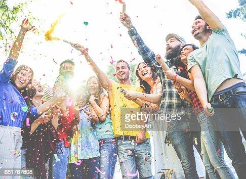 Heureux amis appréciant parti, jetant des confettis et en utilisant des bombes fumigènes couleurs à fête en plein air : Photo