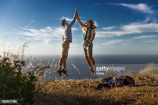 Happy friends giving high-five on hill against sea