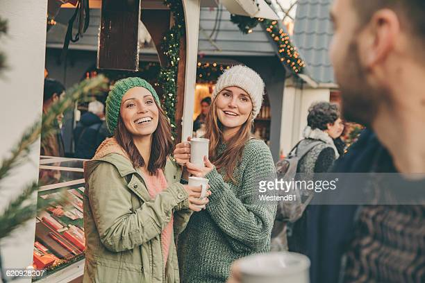 Happy friends having a hot punch on the Christmas Market