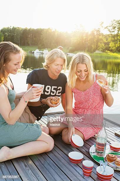 Happy friends having breakfast on pier by lake
