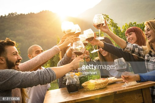 Happy friends having fun an drinking wine in autumn time : Stock Photo