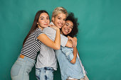 Happy female friends having fun at blue background. Three young women hugging and laughing, slumber party, copy space