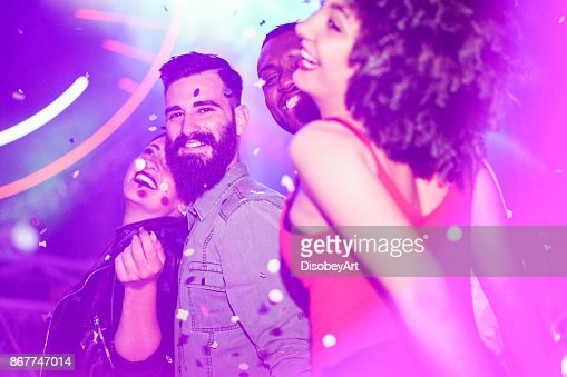 Happy friends having fun in night club with canon ball throwing confetti - Young people enjoying weekend nightlife with original laser lights color - Soft focus on bearded white man - Warm filter : Stock Photo