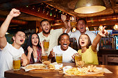 Happy friends having fun in pub watching sport in TV together, drinking beer, cheering for team. Group of people celebrating victory of favorite team, emotionally gesturing hands and shouting goal.