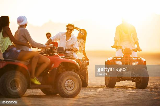 Happy friends having fun on quad bikes at sunset.