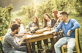 Happy friends having fun outdoor drinking red wine - Young people eating food at harvest time in farmhouse vineyard winery - Youth friendship concept with shallow depth of field - Warm contrast filter