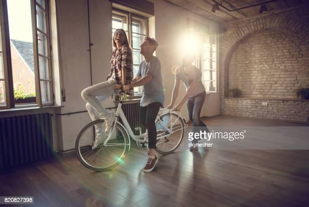 空のアパートに自転車を楽しんで幸せな友達。