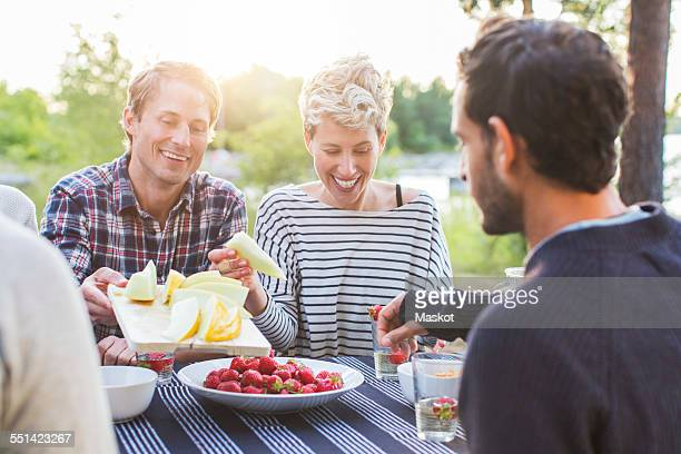 Happy friends having lunch at picnic table
