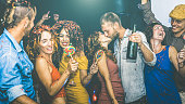 Happy friends having multiracial fun at new year's eve celebration - Young people drinking and dancing at after party in night club - Friendship concept on drunk mood - Focus on yellow cloth woman