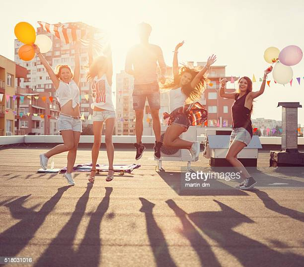 Happy friends jumping from joy on the rooftop