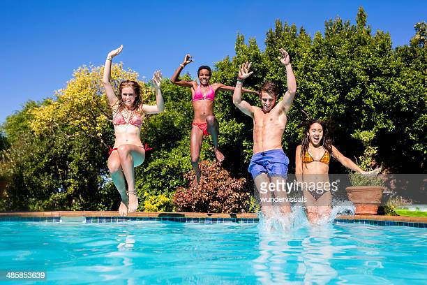 Happy friends jumping into a pool