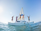 Happy friends jumping off the catamaran boat into the ocean - Young people having fun diving into the sea - Travel, tropical, summer and concept - Soft focus on center guys - Fisheye lens distorsion
