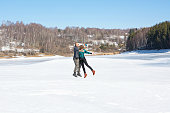Happy friends jumping on the frozen lake