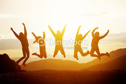 Happy friends jumping sunset mountains : Foto de stock