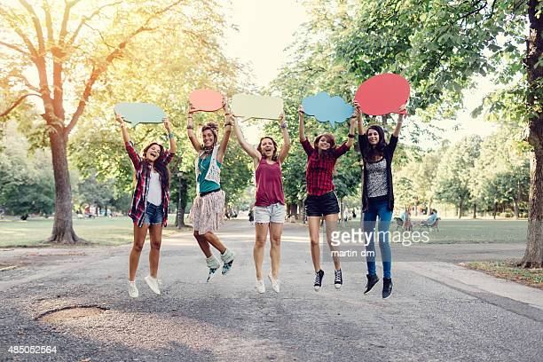 Happy friends jumping with speech bubbles in hands