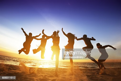 Happy friends jumps beach sunset. Friendship or team concept : Foto stock