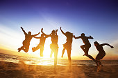 Group of six happy friends jumps at sunset beach backdrop. Friendship or team concept. Space for text