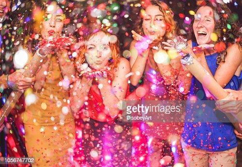 Amigos felices haciendo fiesta lanzando confeti - jóvenes celebrando en la noche del fin de semana - entretenimiento, diversión, fin de año, vida nocturna y fiesta concepto - centrarse en manos de la niña de pelo rojo : Foto de stock