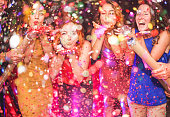 Happy friends making party throwing confetti - Young people celebrating on weekend night - Entertainment, fun, new year's eve, nightlife and fest concept - Focus on red hair girl hands