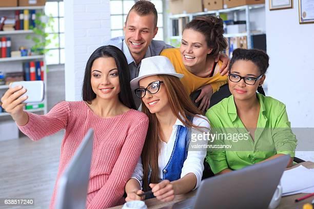 Happy friends making selfie in modern office