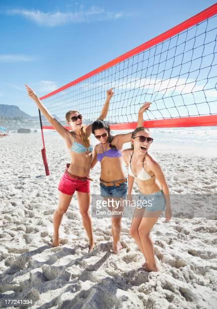 Happy friends on beach volleyball court