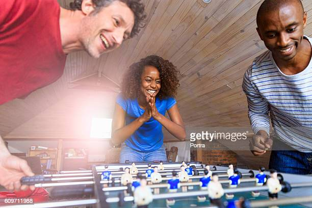 Happy friends playing foosball at home