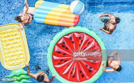 Happy friends playing with ball inside swimming pool - Young people having fun on summer holidays vacation - Travel,holidays,youth,friendship and tropical concept - Seasonal color tones filter : Foto de stock