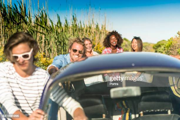 Happy friends pushing car after engine failure