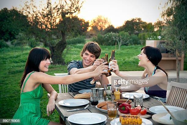 Happy friends sitting at garden table on a barbecue clinking beer bottles