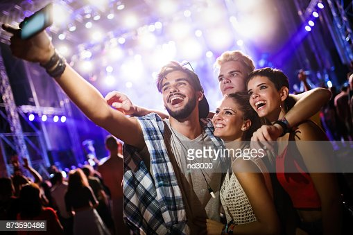 Happy friends taking selfie at music festival : Stock Photo
