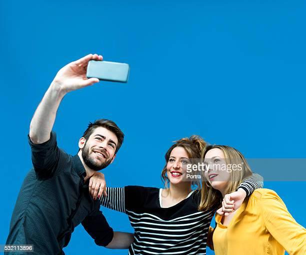 Felices amigos tomando autofoto de teléfono móvil con pantalla azul