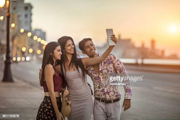Glückliche Freunde nehmen Selfie auf Bürgersteig in Havanna
