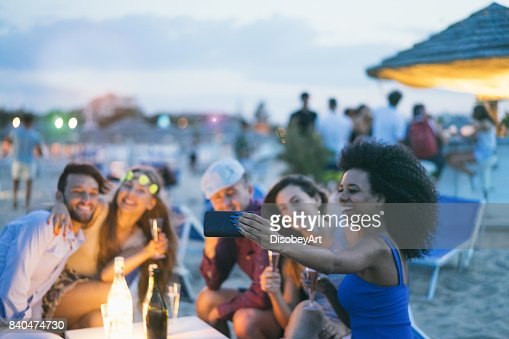 Happy friends taking selfie with smartphone at beach party outdoor - Young people having fun together at kiosk bar drinking champagne  - Focus on african girl hand phone- Youth and summer concept : Foto de stock